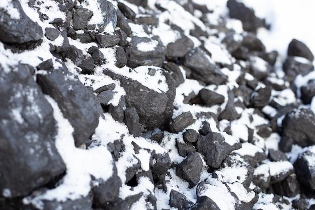 De gros morceaux de charbon sous la neige. combustible pour le poêle en hiver. chauffage d'une maison à la campagne.