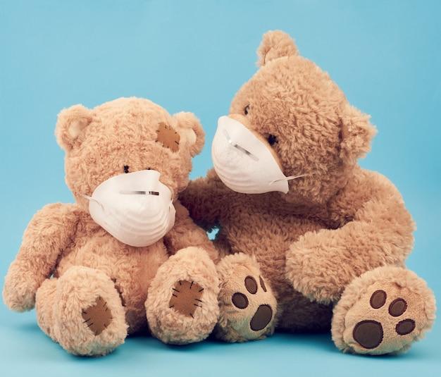 Gros ours en peluche brun sont assis dans des masques médicaux sur fond bleu