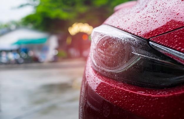 Gros phare d'une voiture moderne rouge avec une goutte de pluie sur fond flou.