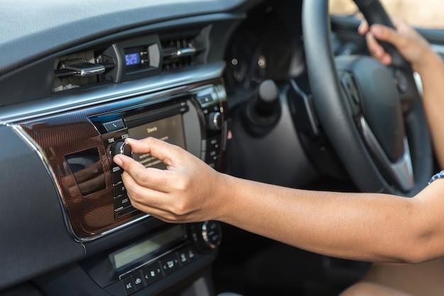 Gros pilote main ajuster le bouton audio dans la voiture