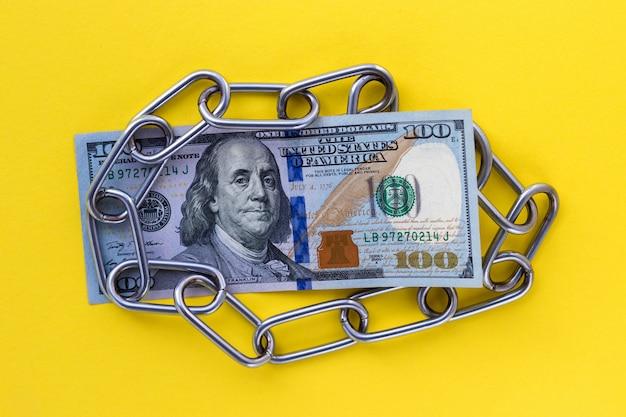 Gros plan de 100 cents dollars américains sous chaîne métallique sur fond jaune