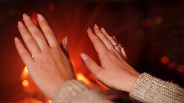 Gros plan 4k footage de jeune femme se réchauffant les mains au feu brûlant dans la cheminée