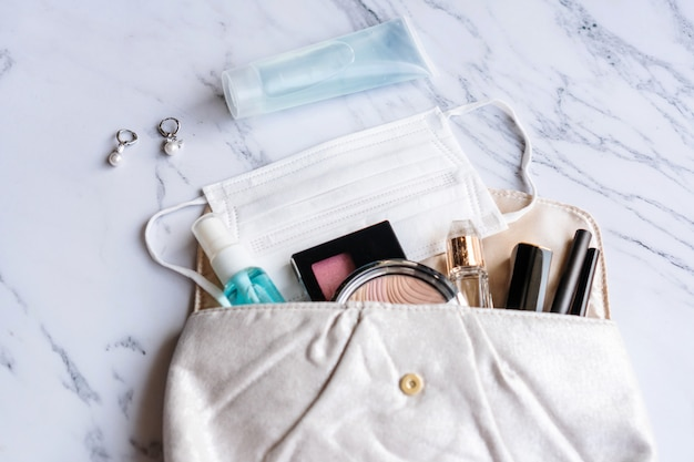 Gros plan des accessoires femme, désinfectant, vaporisateur d'alcool et masque protecteur sur la pochette, concept de beauté. mise à plat