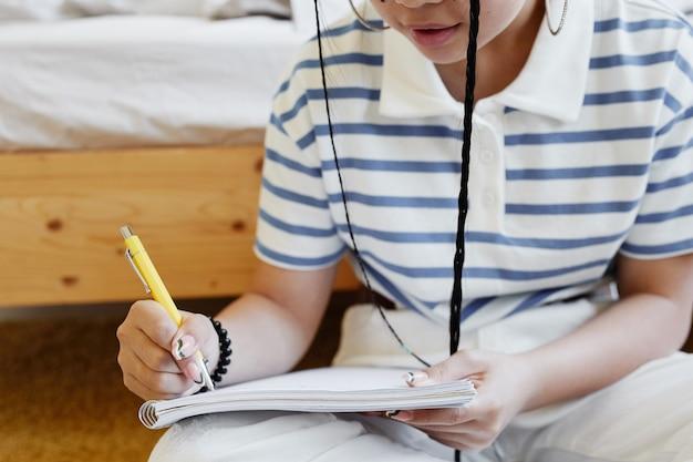 Gros plan sur une adolescente écrivant dans un cahier tout en étant assise par terre à la maison et en faisant ses devoirs, espace de copie