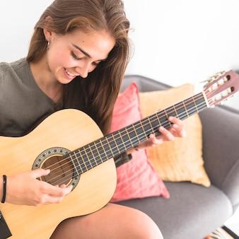 Gros plan d'une adolescente heureuse jouant de la guitare