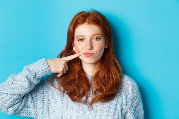 Gros plan d'une adolescente impertinente aux cheveux rouges, pointant sur sa joue et regardant la caméra, debout sur fond bleu.