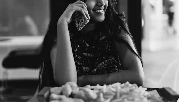 Gros plan d'une adolescente parlant sur un téléphone en mangeant le concept de culture des jeunes frites