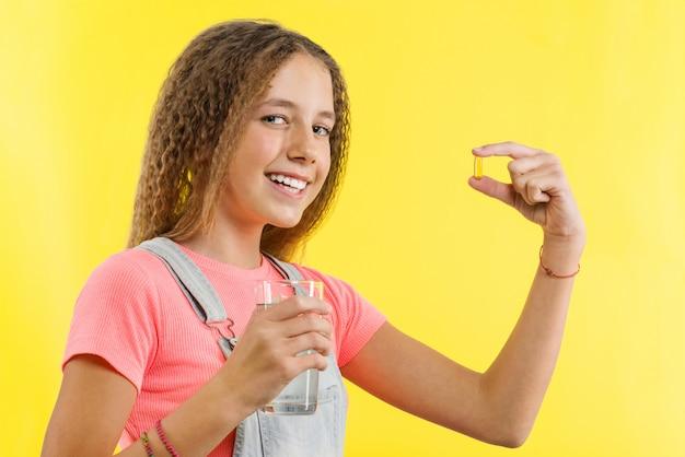 Gros plan d'une adolescente prenant une pilule avec de l'huile de foie de morue oméga-3