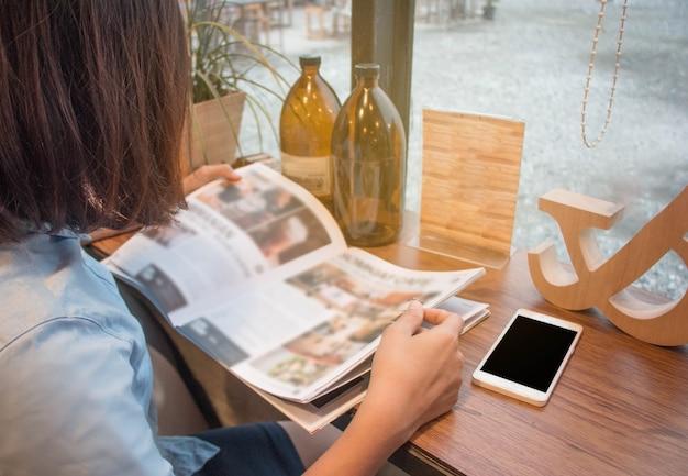 Gros plan adolescente tenant et lire magazine au café
