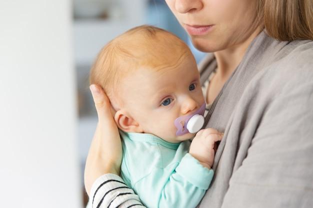 Gros plan de l'adorable bébé aux cheveux roux adorable avec sucette