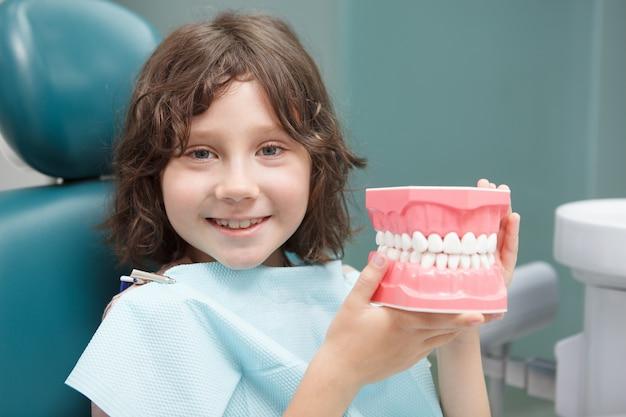 Gros plan d'un adorable petit garçon souriant à la caméra, tenant un modèle dentaire, assis au bureau du dentiste