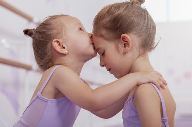 Gros plan d'une adorable petite ballerine embrassant sa sœur aînée sur le front