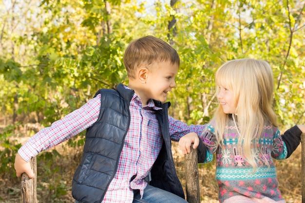 Gros plan d'adorables petits enfants blancs en tenue de mode d'automne souriant les uns aux autres dans le parc avec des arbres verts à l'arrière-plan.