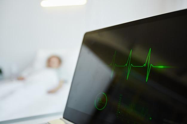 Gros plan sur l'affichage du moniteur cardiaque à l'hôpital avec un enfant allongé dans son lit en arrière-plan, espace pour copie