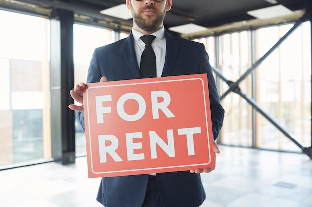 Gros plan de l'agent immobilier en costume tenant une pancarte dans ses mains en se tenant debout au bureau moderne, il suggère un bureau à louer