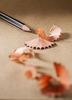Gros plan aiguiser un crayon noir sur du papier brun