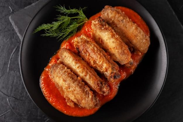 Gros plan d'ailes de buffle fraîchement cuit avec sauce tomate et tomates