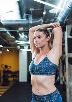 Gros plan, de, a, ajustement, jeune femme, faire, stretching, exercice, dans, gymnase