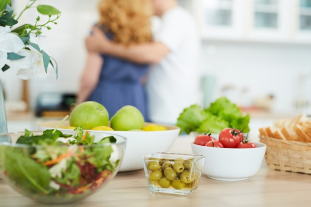 Gros plan d'aliments sains et de collations sur le comptoir de la cuisine avec une silhouette floue de couple cuisine en arrière-plan, copiez l'espace