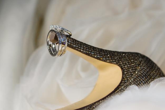 Gros plan des alliances sur les chaussures de la mariée