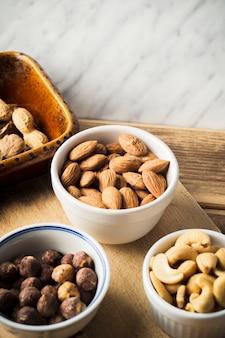 Gros plan d'amande; noisette; noix de cajou et cacahuètes dans un bol sur une planche à découper