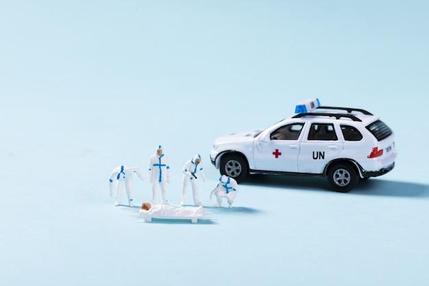 Gros plan sur une ambulance jouet et des ambulanciers paramédicaux aidant un patient