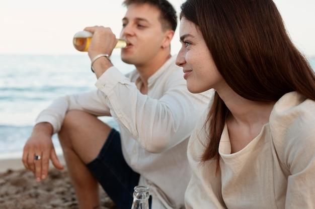 Gros plan d'amis assis sur la plage ensemble
