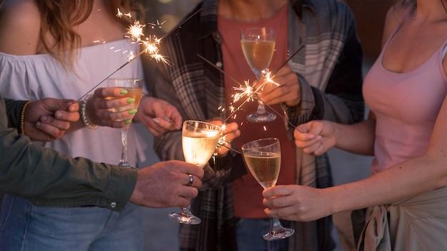 Gros plan d'amis faisant la fête avec des feux d'artifice