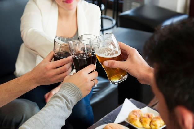 Gros plan des amis griller des verres de boissons chaudes au bar