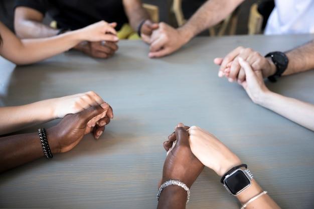 Gros plan des amis interraciaux en prière