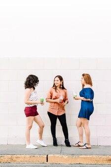 Gros plan sur des amis multiethniques tenant des gobelets en plastique jetables avec du jus