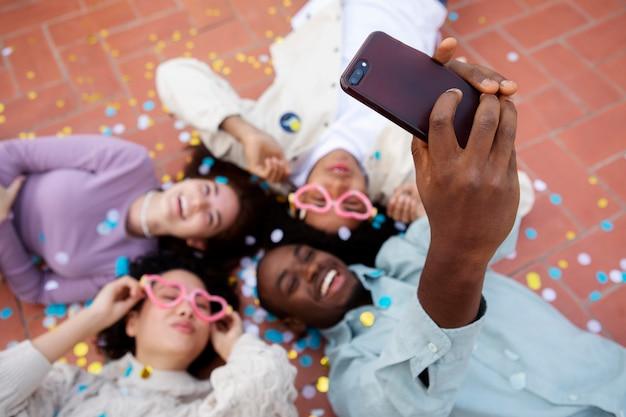 Gros plan des amis sur le sol en prenant un selfie