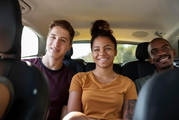 Gros plan sur des amis souriants en voiture
