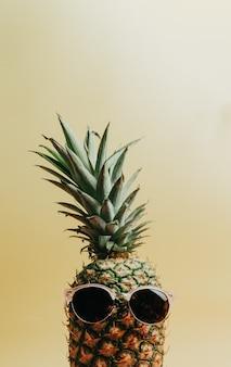 Gros plan d'un ananas avec une paire de lunettes de soleil sur fond jaune pastel, espace de copie, concept d'été et de vacances