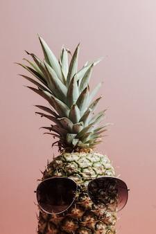 Gros plan d'un ananas avec une paire de lunettes de soleil sur fond rose pastel, espace de copie, concept d'été et de vacances