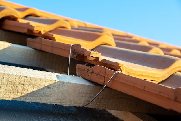 Gros plan sur une ancre de montage en métal pour l'installation de tuiles de toiture en céramique jaune montées sur des planches de bois couvrant le toit d'un bâtiment résidentiel en construction.