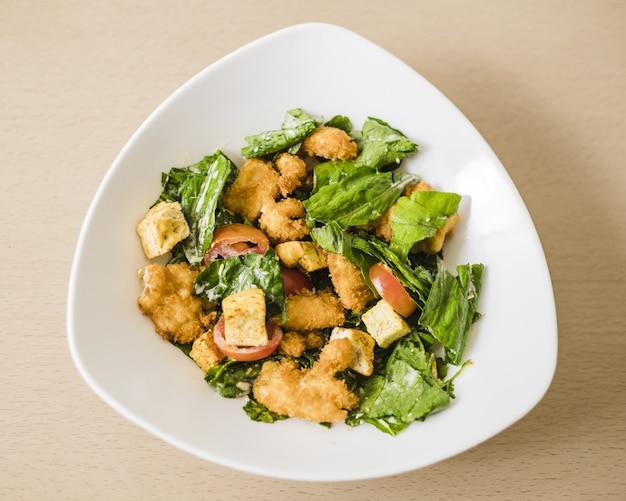 Gros plan sur un angle élevé d'une salade césar dans un bol blanc