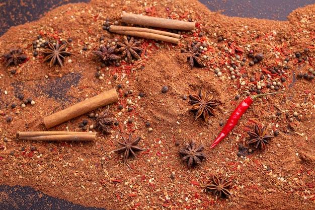 Gros plan de l'anis étoilé et de la cannelle et du poivre moulu se trouvent sur le concept de nourriture épicée de table et
