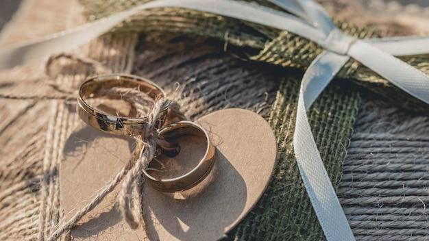 Gros plan des anneaux de mariage dorés attachés à un textile en forme de coeur marron
