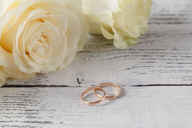 Gros plan des anneaux de mariage sur fond de roses