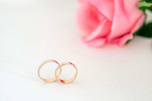 Gros plan sur les anneaux de mariage en or avec une rose
