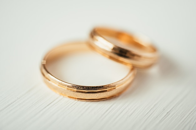 Gros plan des anneaux d'or de mariage qui se croisent sur un fond en bois blanc