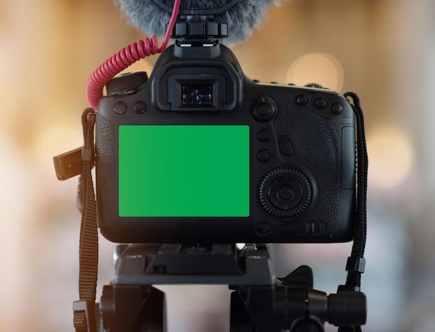 Gros plan de l'appareil photo sur un trépied avec un écran lcd vert et un microphone d'enregistrement