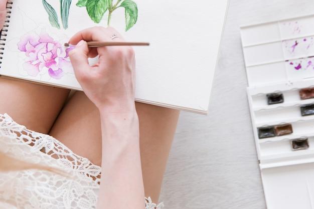 Gros plan sur aquarelle sketch et main. travail de peintre avec image. oeuvre colorée de fleur sur papier blanc. peinture d'artiste avec palette et pinceau.