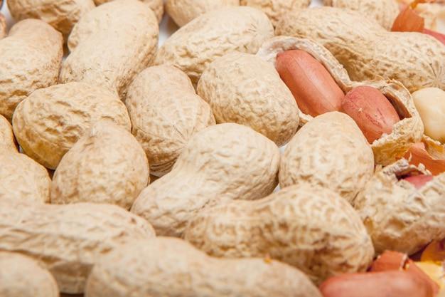Gros plan d'arachides pelées de haricots dans la coquille