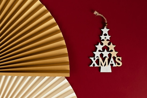 Gros plan d'un arbre de noël décoratif fait d'étoiles dorées avec un éventail en papier. décorations de noël modernes et élégantes sur mur cramoisi