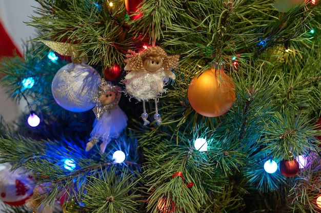 Gros plan d'arbre de noël avec des ornements. arbre de noël avec des décorations d'anges, de boules et de lumières se bouchent. idées de décoration de noël.