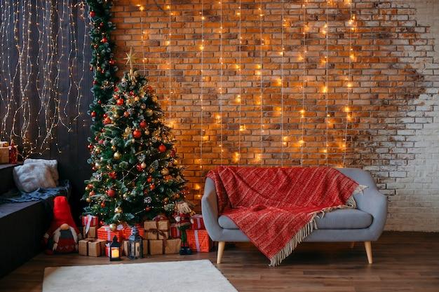Gros plan d'un arbre de noël vert avec des boules de décoration rouge et des boîtes à cadeaux, contre un mur de briques avec des guirlandes jaunes, un canapé gris dans le.