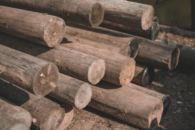 Gros plan des arbres coupés, des cabanes en rondins, des rondins reposent un tas sur la route