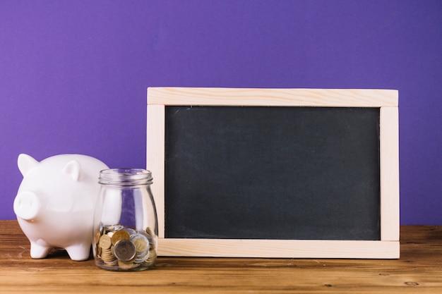Gros plan de l'ardoise; tirelire avec des pièces de monnaie dans un pot sur un bureau en bois
